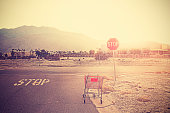 Retro toned empty shopping trolley left on street at sunset, Palm Springs, USA.