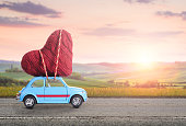 Blue retro toy car delivering heart for Valentine's day against blurred rural Tuscany sunset landscape