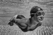 'Young woman swimming underwater. Retro style black and white processing, increased contrasts, very fine grain added'