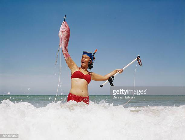 Retro woman holding fresh catch in beach surf