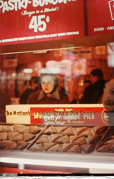 Retro woman looking into pizza shop