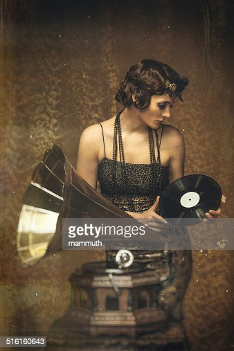 Retro woman playing a vinyl on gramophone -scratched vintage image.