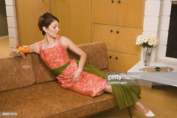 Retro woman relaxing with cocktail
