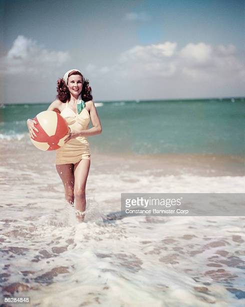 Retro woman walking in surf holding colorful beach ball