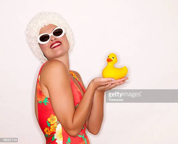 A retro woman wearing sunglasses and a hat holds a large rubber ducky, smiling to the viewer