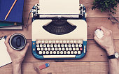 Top view retro typewriter office desk setting with male hands acting frustrated about no inspiration to write