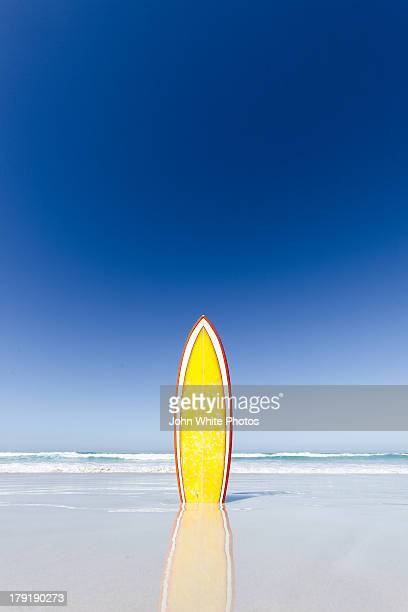 Retro yellow surf board and blue sky. Australia.