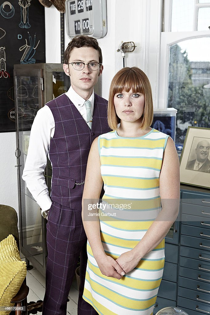 Retro-styled couple standing, looking to camera. : Stock Photo