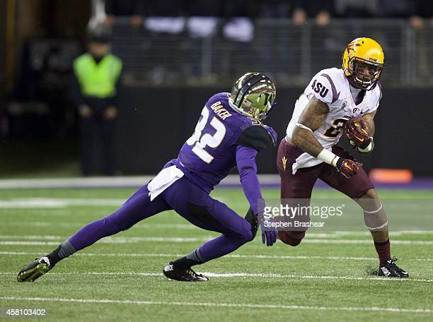 Returner Jaelen Strong of the Arizona State Sun Devils runs back a punt as defensive back Budda Baker of the Washington Huskies moves in for the...