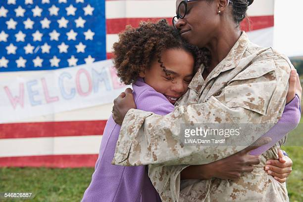 Returning Black soldier hugging daughter