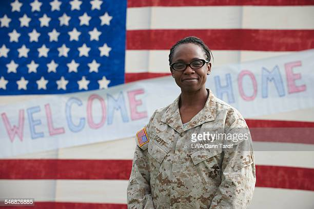 Returning Black soldier standing near American flag welcome home sign