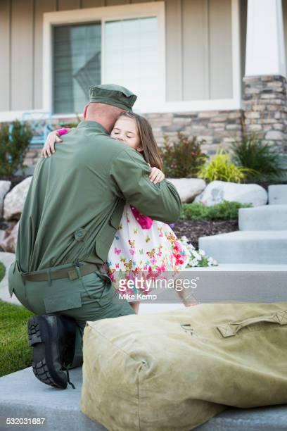 Returning Caucasian soldier hugging daughter on front stoop
