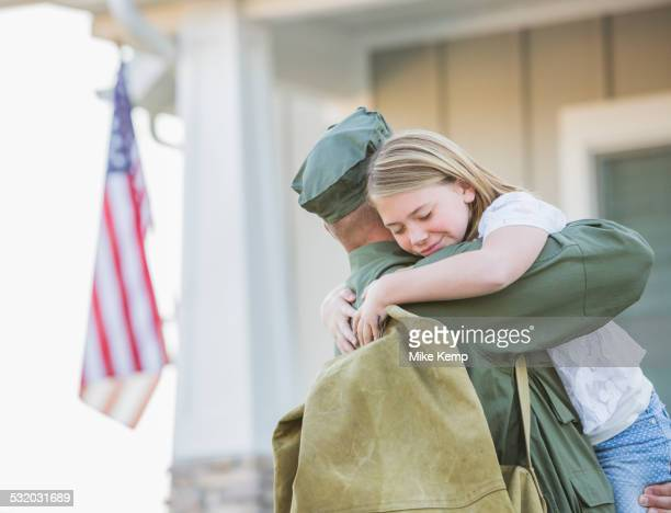 Returning Caucasian soldier hugging daughter