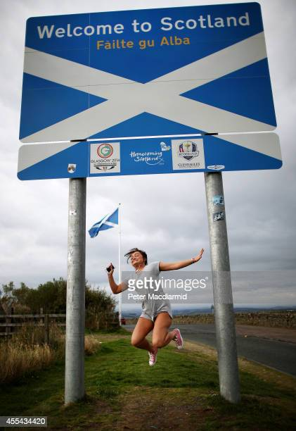 A returning Scottish woman jumps as her friend takes a photograph on the border with England on September 14 2014 in Carter Bar Scotland The latest...