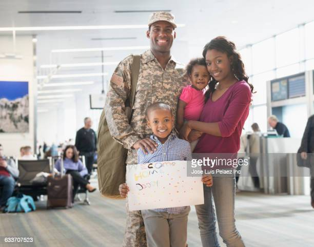 Returning soldier and family smiling in airport