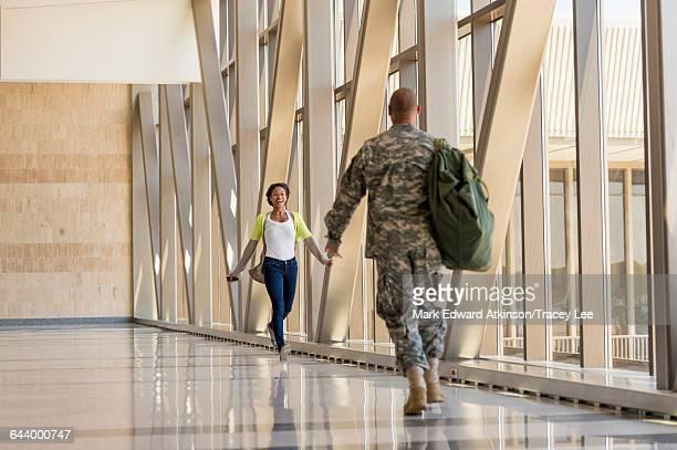 Returning soldier greeting girlfriend in airport