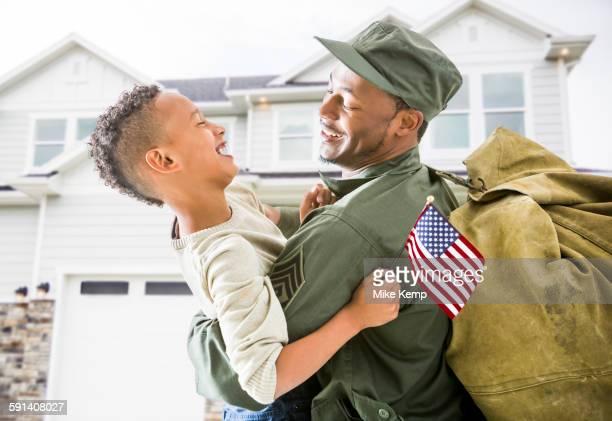 Returning soldier hugging patriotic son outside house
