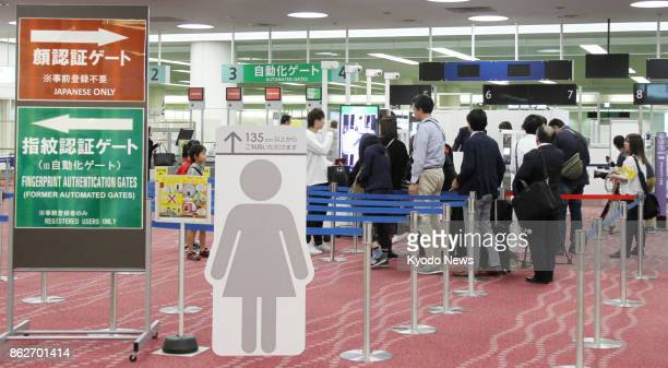Returning travelers line up to pass through automated facial recognition gates newly launched at Haneda airport in Tokyo on Oct 18 2017 Japan plans...