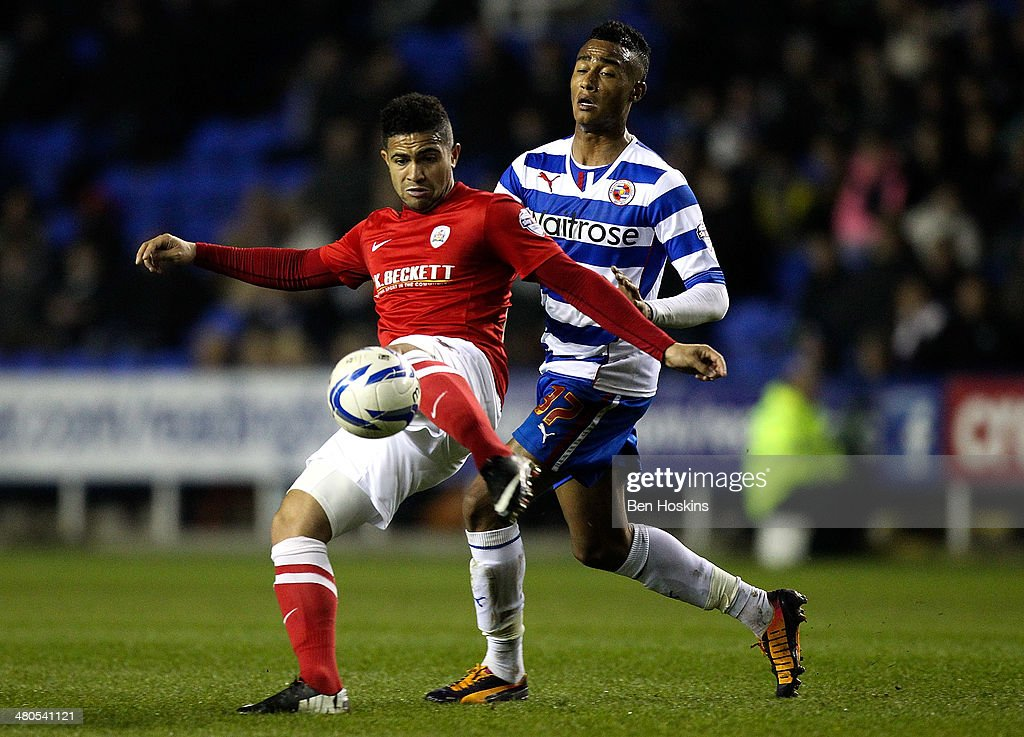 Reuben Noble-Lazarus (L) of Barnsley clears the ball under pressure from Jordan Obita of Reading during the Sky Bet Championship match between Reading and Barnsley at Madejski Stadium on March 25, 2014 in Reading, England,
