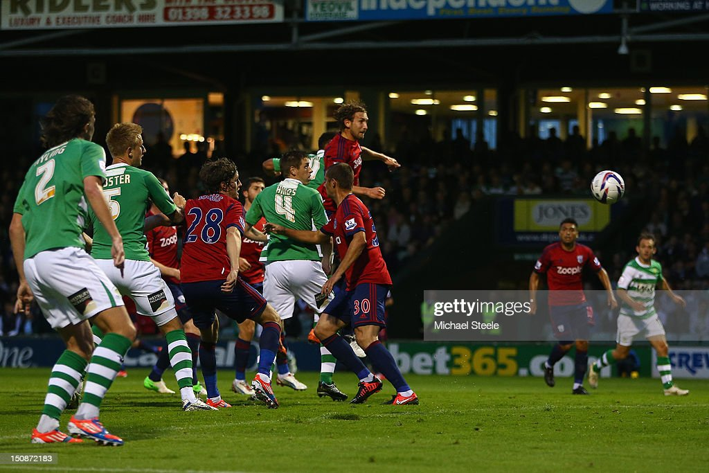 Reuben Reid of Yeovil Town scores the opening goal as Billy Jones of West Bromwich Albion challenges during the Capital One Cup second round match...