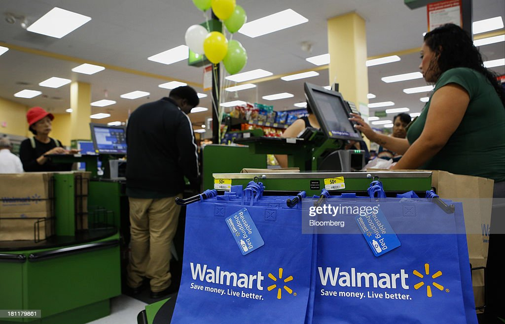 Reusable shopping bags hang as a cashier checks out customers during the grand opening of a Wal-Mart Stores Inc. location in the Chinatown neighborhood of Los Angeles, California, U.S., on Thursday, Sept. 19, 2013. Wal-Mart Stores Inc. will phase out 10 chemicals it sells in favor of safer alternatives and disclose the chemicals contained in four product categories, the company announced Sept. 12. Photographer: Patrick T. Fallon/Bloomberg via Getty Images