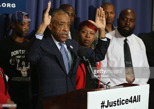 Rev Al Sharpton raises his hands while flanked by Lesley McSpadden and Michael Brown Sr parents of Michael Brown who was killed by police in Ferguson...