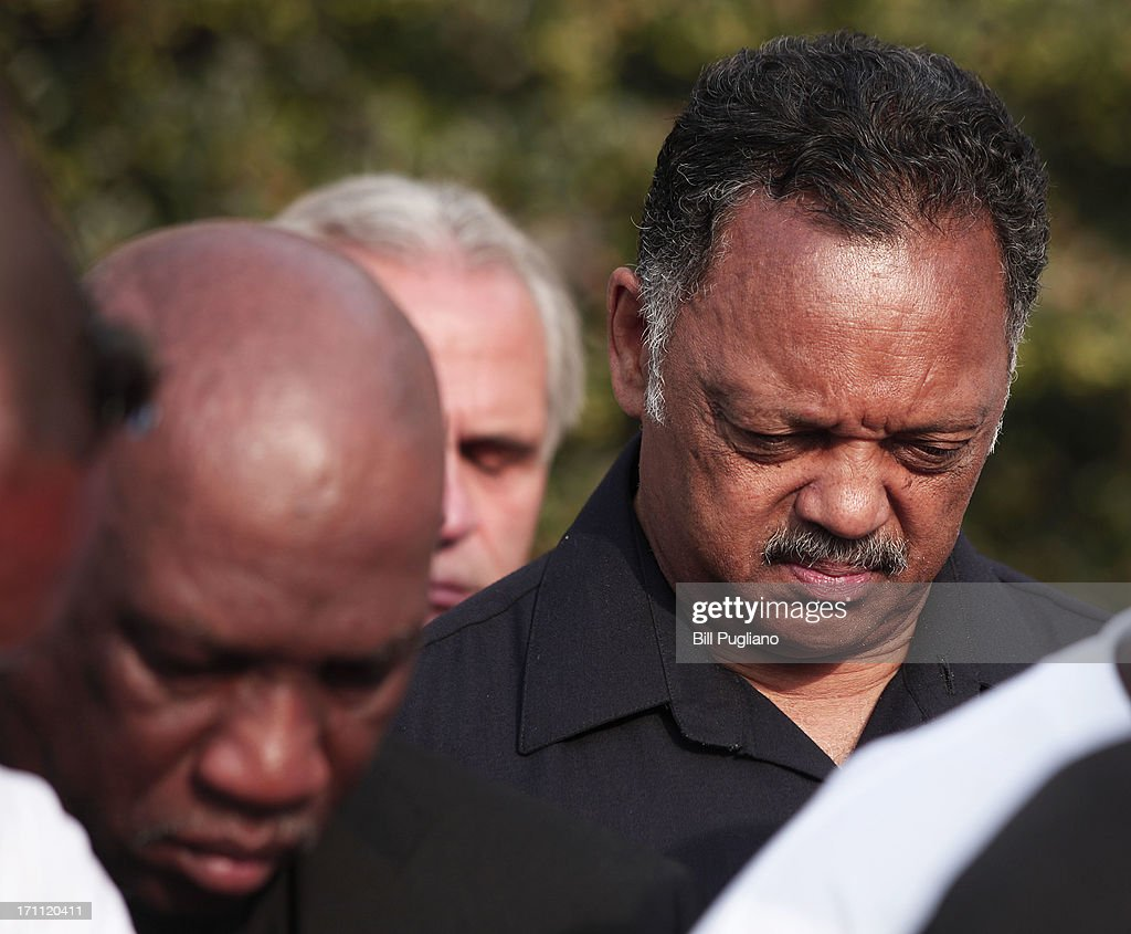 Rev. Jesse Jackson (right) bows his head as a prayer is said at a press conference before marching in the 50th Anniversary Commemorative Freedom Walk June 22, 2013 in Detroit, Michigan. The march commerated the 50th anniversary of civil rights leader Dr. Martin Luther King's Walk To Freedom, which followed the same route through Detroit back in 1963. Guests at the event included Martin Luther King III (Dr. KIng's son), NAACP President Ben Jealous, Rev. Jesse Jackson, Rev. Al Sharpton, Dr. King's advisor Rev. C.T. Vivian, and comedian Dick Gregory.