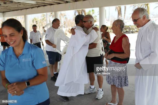 Rev Jets Medina and Deacon Richard Turcotte hold a mass for their congregation of St Peter Catholic Church under a pavillion after their church was...