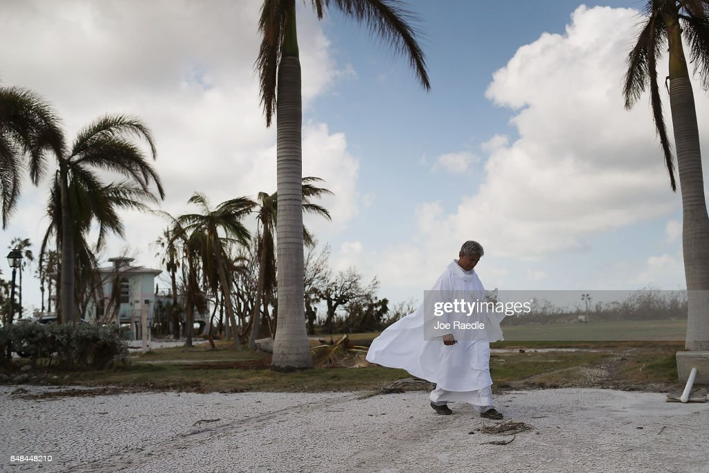 Rev. Jets Medina walk to a pavillion as he prepares to lead a mass for their congregation of St. Peter Catholic Church after their church was damaged by hurricane Irma on September 17, 2017 in Big Pine Key, Florida. The Federal Emergency Management Agency has reported that 25-percent of all homes in the Florida Keys were destroyed and 65-percent sustained major damage when they took a direct hit from Hurricane Irma.