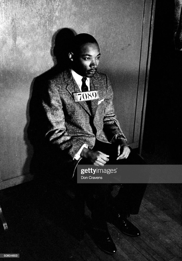 Rev. Martin Luther King Jr., director of segregated bus boycott, with 7080 sign across his chest for police mug shot, sitting on chair against wall in station house after his arrest for directing city-wide boycott of segregated buses.