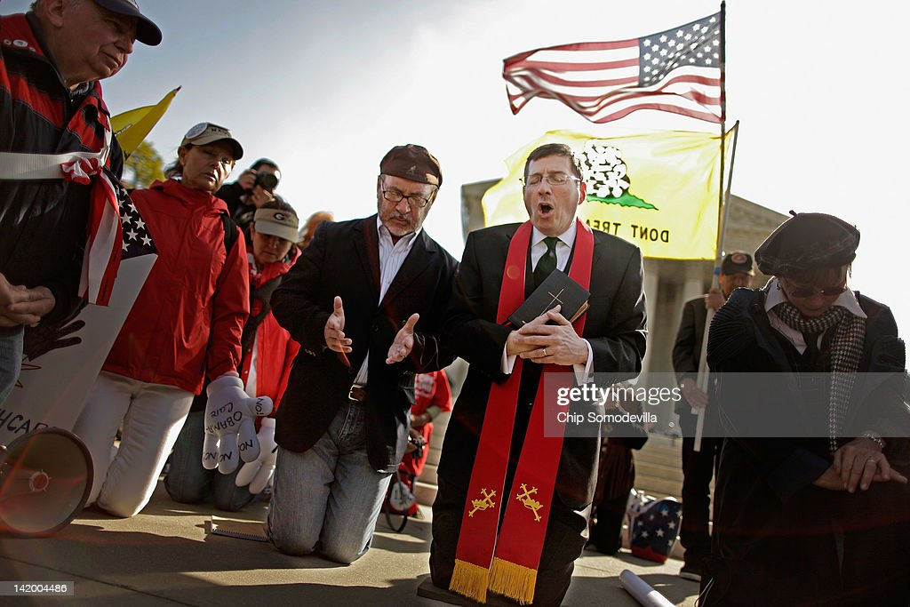 Rev. Rob Schneck (C) and Rev. <a gi-track='captionPersonalityLinkClicked' href=/galleries/search?phrase=Patrick+Mahoney&family=editorial&specificpeople=220867 ng-click='$event.stopPropagation()'>Patrick Mahoney</a> (4th R) lead people in prayer outside the U.S. Supreme Court on the third day of oral arguements over the constitutionality of the Patient Protection and Affordable Care Act March 28, 2012 in Washington, DC. Today is the last of three days the high court set to hear arguments over the act.