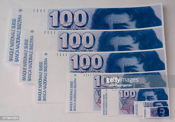 Revaluation devaluation turbulences around the Swiss franc Our picture shows 100 hundred Swiss franc banknotes in large and small illustrations