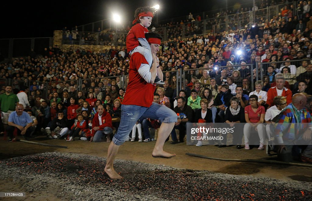 A reveler carries a child on his back while rushing through burning embers during the night of San Juan in San Pedro Manrique, Soria province in northern Spain early on June 24, 2013. The ritual consists in starting a bonfire and for the locals to step barefoot on hot coals without burning the soles of their feet, and most times with someone on their back.