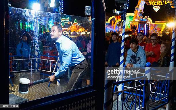 A reveler checks his power at a funfair amusement stall during nighttime of the opening day of the 2015 Oktoberfest on September 19 2015 in Munich...