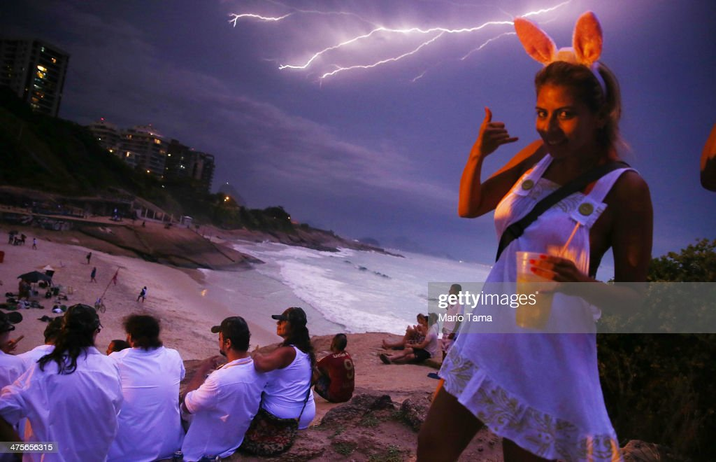 Reveler Daniela Solares from Bolivia walks past the camera as lightning strikes over Copacabana Beach during the Vem Ni Mim Que Sou Facinha street carnival bloco on February 28, 2014 in Rio de Janeiro, Brazil. Carnival is the grandest holiday in Brazil, annually drawing millions in raucous celebrations.