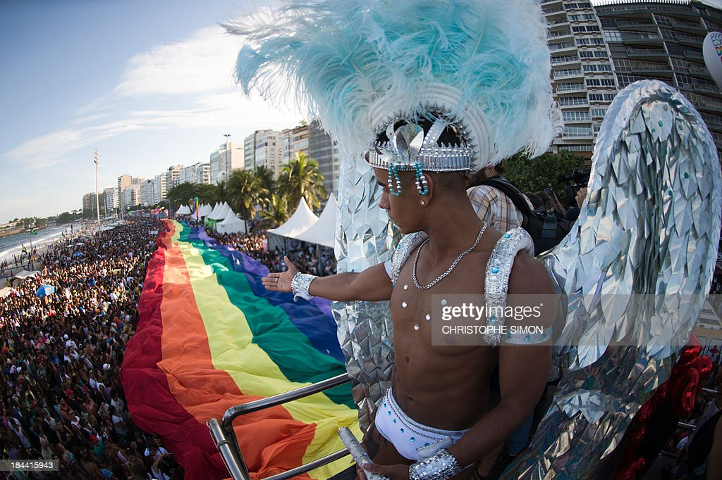 A reveler disguised as an angel looks at Copacabana beach during the gay pride parade in Rio de Janeiro, Brazil on October 13, 2013. AFP PHOTO / CHRISTOPHE SIMON