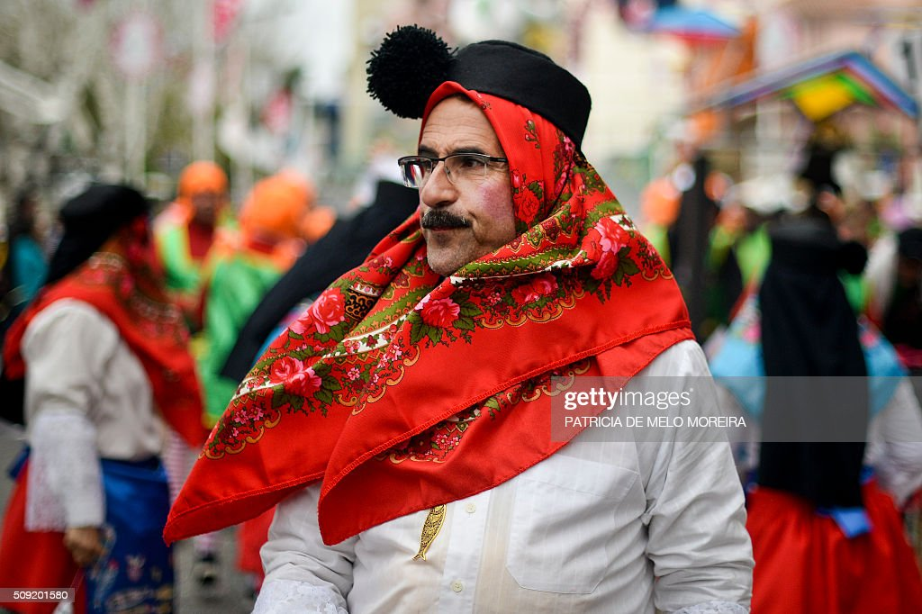 A reveler dressed as typical Portuguese fish seller walks during the annual Carnival Parade at Torres Vedras, on February 9, 2016. Torres Vedras Carnival is the most 'portuguese' of all the carnivals in Portugal is known by the strong political and football satire of the revealers and their floats. / AFP / PATRICIA DE MELO MOREIRA