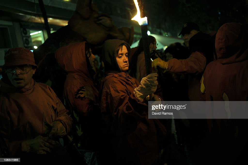A reveler dressed up as a devil holds a torch before taking part in a 'Correfoc' or 'Fire-runs' during the Sant Antoni neighborhood celebrations on January 23, 2011 in Barcelona, Spain. 'Correfoc' is a traditional Catalan festival dated from the 12th century where people dress up as a devil to run dancing among firecrackers.