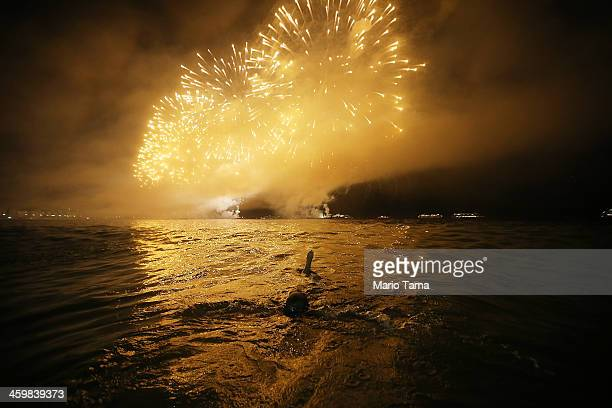A reveler floats while watching fireworks explode minutes after midnight along Copacabana Beach during New Year's celebrations on January 1 2014 in...