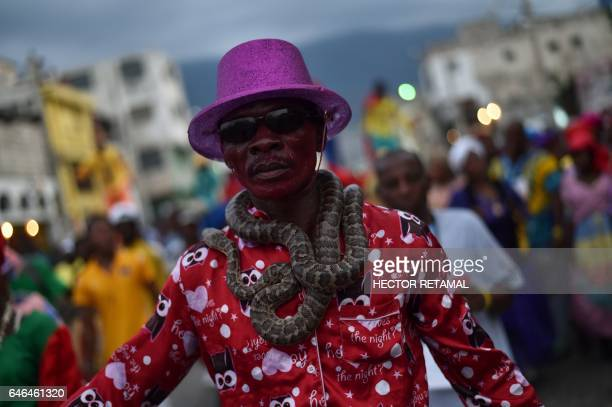 A reveler garlanded with snakes performs in the third and final day of Carnival in the capital of Haiti PortauPrince on February 28 2017 Dancers...