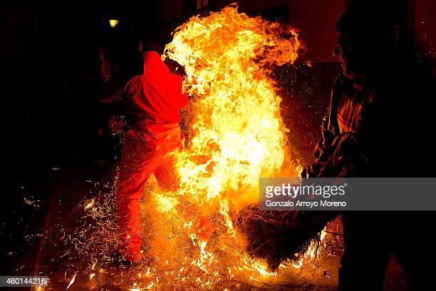A reveler hits a man with a burning broom during the 'Los Escobazos' Festivial on December 7 2014 in Jarandilla de la Vera Spain The origin of this...
