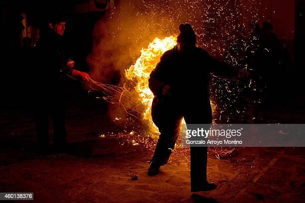 A reveler is hit by a man waving a burning broom during the 'Los Escobazos' Festivial on December 7 2014 in Jarandilla de la Vera Spain The origin of...
