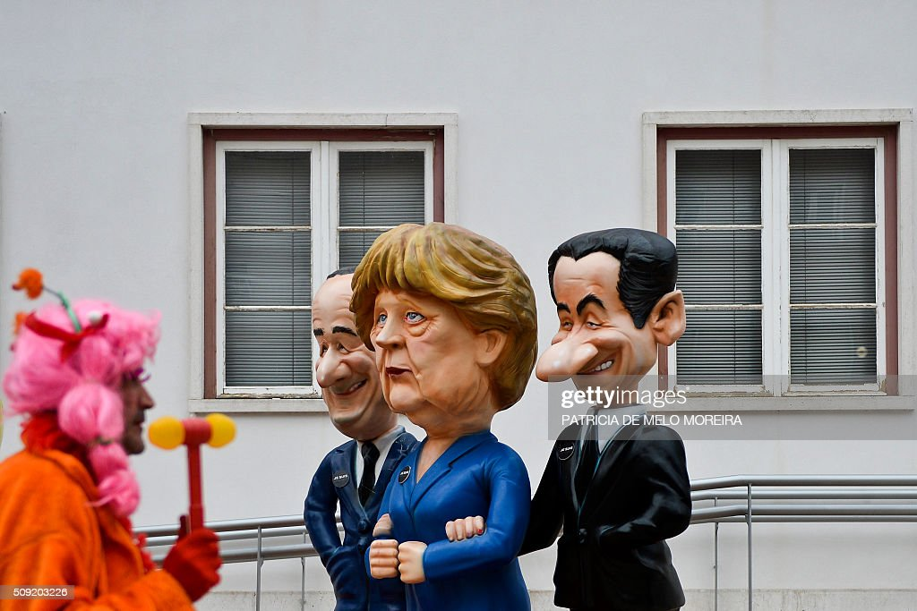 A reveler passes by cartoon figures of French president Francois Hollande (L) German Chanceller Angela Merkel (C) and French former President Nicolas Sarkozy (R) during the annual parade in Torres Vedras on February 9, 2016. The Torres Vedras Carnival is allegedly the 'most Portuguese' of all the carnivals in the country recognized by the strong political and football satire of the revelers disguises and their floats. / AFP / PATRICIA DE MELO MOREIRA