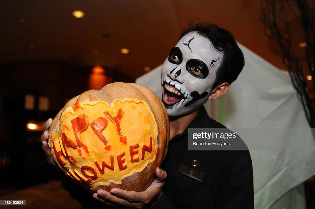 A reveler poses with a jacko'lantern at a Halloween party at Sheraton Surabaya Hotel on October 31 2013 in Surabaya Indonesia Revelers across the...