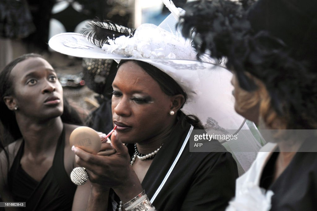 A reveler puts lipstick before participating in an 'Ash Wednesday' carnival parade in Fort-de-France on the French Caribbean island of Martinique, on February 13, 2013.