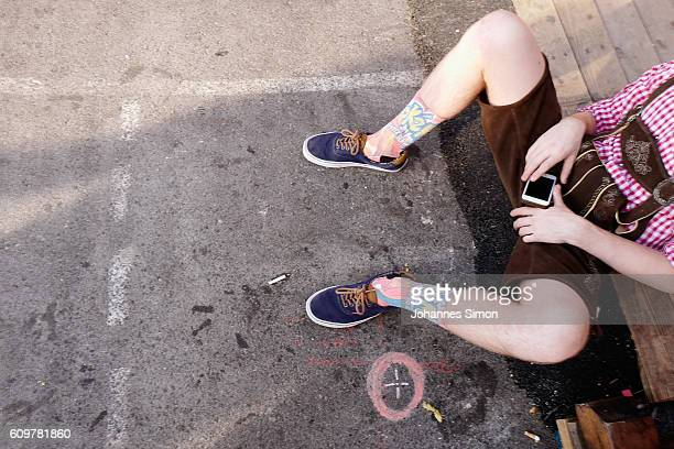 A reveler sits on the floor during day 6 of the 2016 Oktoberfest beer festival at Theresienwiese on September 22 2016 in Munich Germany The 2016...