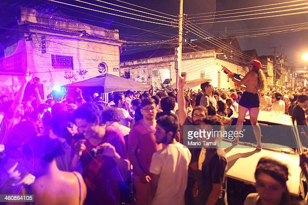 A reveler sprays water on the crowd at a street party thrown one block away from Rio's main red light district Vila Mimosa on January 5 2014 in Rio...
