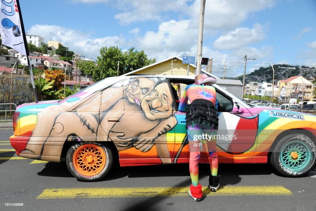 A reveler stands in front of a car bearing a drawing mocking French President Francois Hollande during the Carnival parade in the streets of Fort-de-France on the French Caribbean island of Martinique, on February 10, 2013. The Carnaval started on February 9, 2013 and will run until Ash Wednesday on February 13, 2013 when Vaval, a giant papier-mache figure symbolizing the king of the carnival, is burned. AFP PHOTO/ JEAN-MICHEL ANDRE