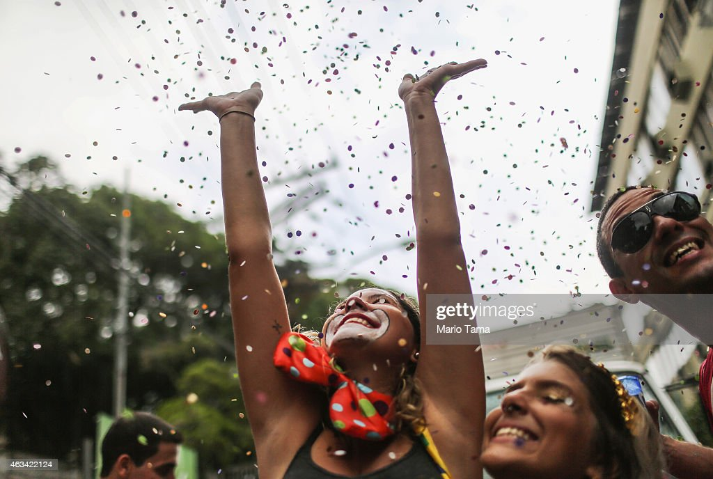 A reveler tosses confetti into the air while taking a group selfie at the 'Ceu na Terra' (Sky on Earth) street parade during Carnival festivities on February 14, 2015 in Rio de Janeiro, Brazil. Carnival runs this year February 13-17.