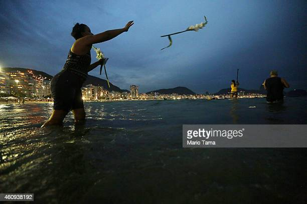 A reveler tosses flowers into the ocean as traditional offerings to the Brazilian sea goddess Iemanja during New Year's Eve festivities on Copacabana...